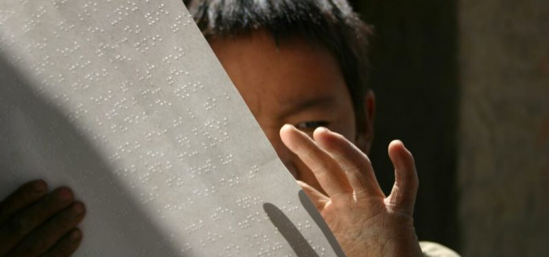 One student reading braille holding the paper up covering half of his face
