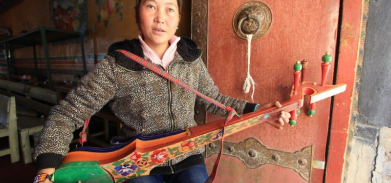 A young blind girl playing traditional tibet instrument