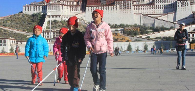 Blind children walking on the street of Tibet using white cane